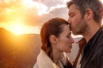 Mann küsst Frau liebevoll auf die Stirn