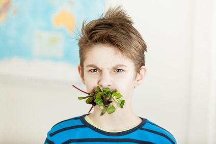 Ein Junge hat Salat im Mund