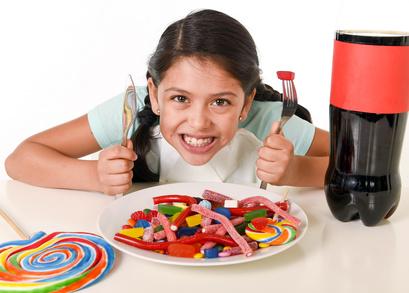 Kleines Mädchen mit Süßigkeiten auf dem Tisch